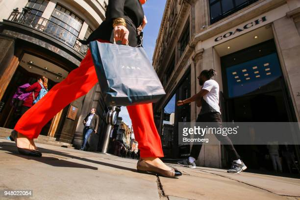 A shopper caries a Zara clothing retailer bag as shes passes a Gap Inc retail store left and a Coach retail store in Regent Street in London UK on...