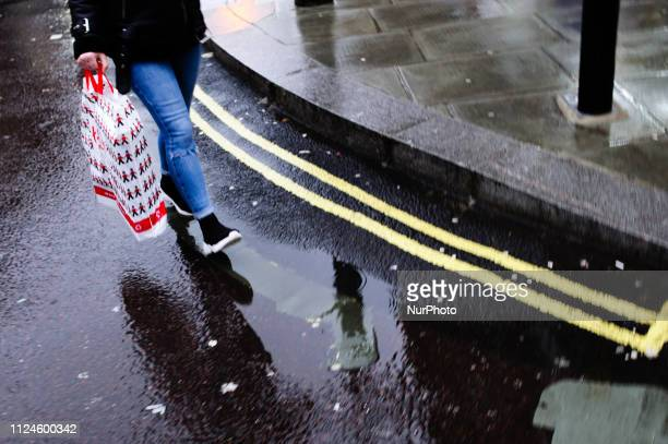 A shopper carries a bag from toy retailer Hamleys along Oxford Street on a wet afternoon in London England on February 8 2019 February 15 sees the...