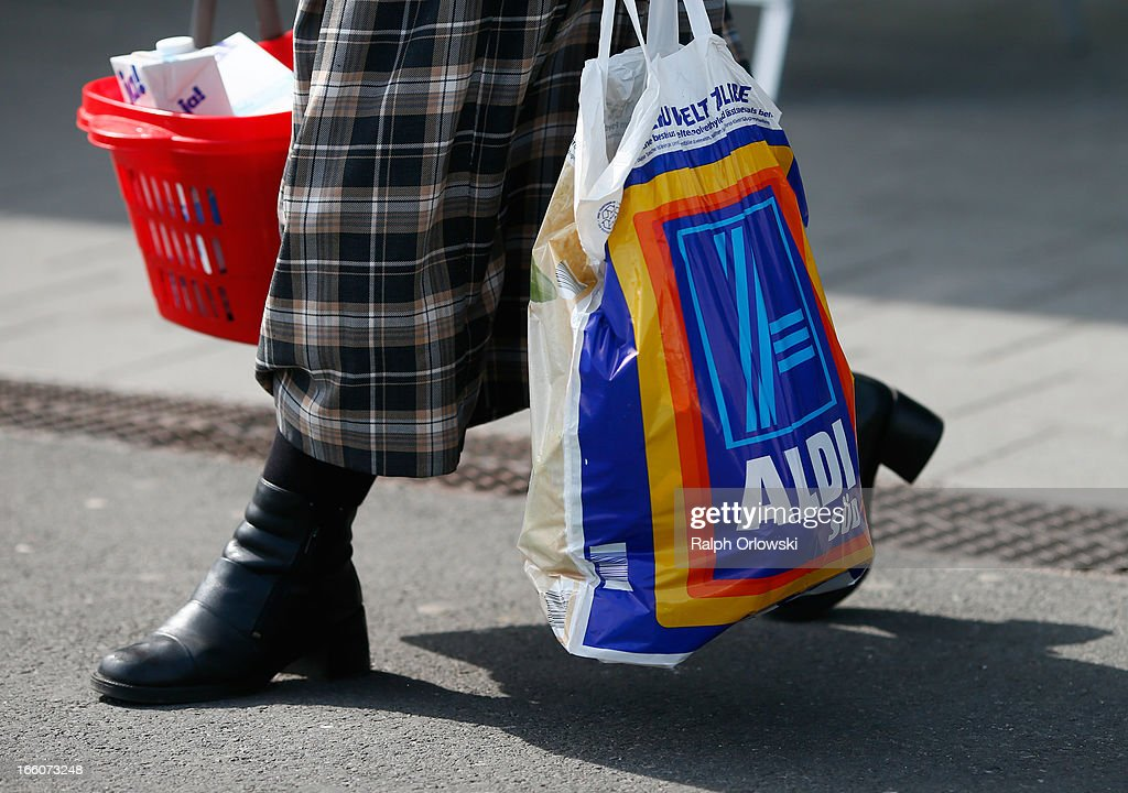 A shopper carries a bag of groceries from an Aldi store on April 8, 2013 in Frankfurt, Germany. Aldi, which today is among the world's most successful discount grocery store chains, will soon mark its 100th anniversary and traces its history back to Karl Albrecht, who began selling baked goods in Essen on April 10, 1913 and founded the Aldi name by shortening the phrase Albrecht Discount. His sons Karl Jr. and Theo expanded the chain dramatically, creating 300 stores by 1960 divided between northern and southern Germany, with Aldi Nord and Aldi Sued, respectively. Today the two chains have approximately 4,300 stores nationwide and have also expanded into other countries across Europe and the USA. Aldi Nord operates in the USA under the name Trader Joe's.