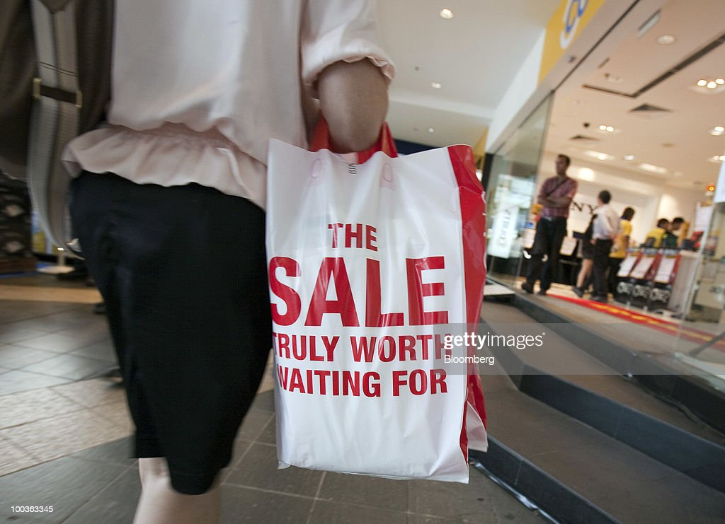 A shopper carries a bag past a shopping mall in Singapore, on Monday, May 24, 2010. Singapore's consumer prices rose at the fastest pace in 14 months in April as an accelerating economy and a booming labor market boosted housing and transportation costs. Photographer: Charles Pertwee/Bloomberg via Getty Images