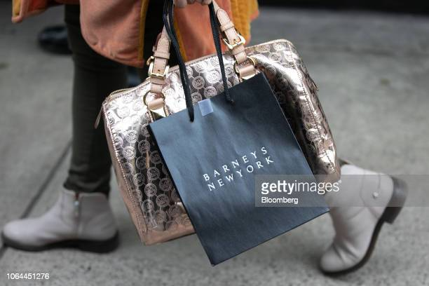 A shopper carries a Barneys New York Inc retail bag while walking along Madison Avenue in New York US on Wednesday Nov 21 2018 The National Retail...