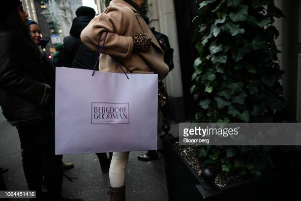 A shopper carries a Bergdorf Goodman Inc retail bag while looking at a holiday window display on Madison Avenue in New York US on Wednesday Nov 21...
