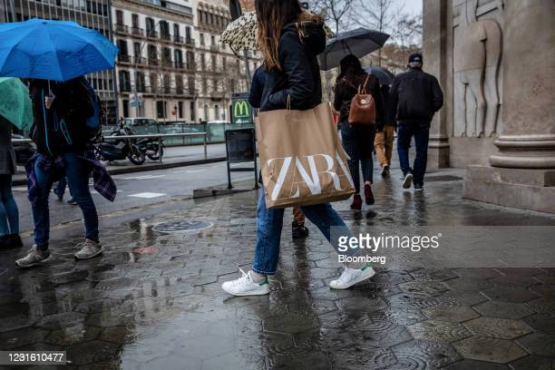Shopper carries a branded bag from a Zara clothing store, operated by Inditex SA, in Barcelona, Spain, on Monday, March 8, 2021. Inditex will report...