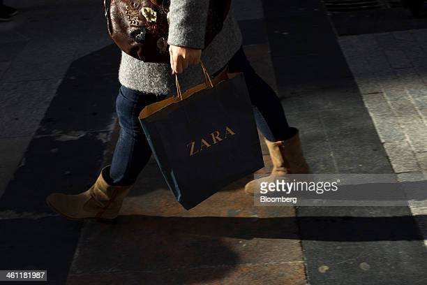04b0c4e8 A shopper carries a branded shopping bag from Zara operated by Inditex SA  along a street