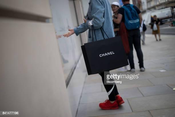 A shopper carries a Chanel SA luxury goods branded shopping bag as she walks along New Bond Street in central London UK on Thursday Aug 31 2017 UK...
