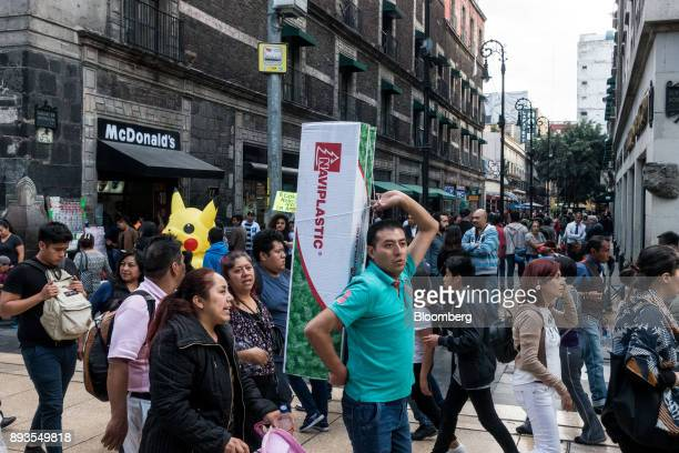 A shopper carries a Christmas tree box near the main square in Mexico City Mexico on Monday Nov 20 2017 The National Institute of Statistics and...