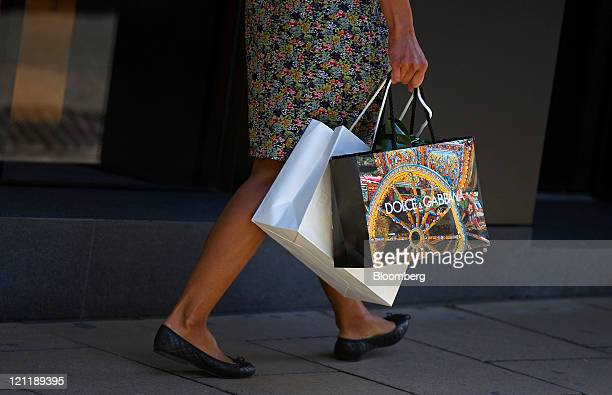 Shopper carries a Dolce & Gabbana Srl-branded shopping bag in Old Bond Street in central London, U.K., on Monday, Aug. 15, 2011. U.K. Inflation...