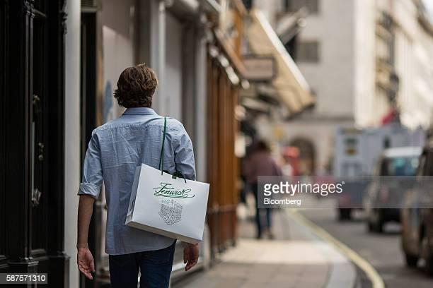A shopper carries a Fenwick Ltd department store shopping bag on Bond Street in London UK on Monday Aug 8 2016 Consumers spent more on new clothes...
