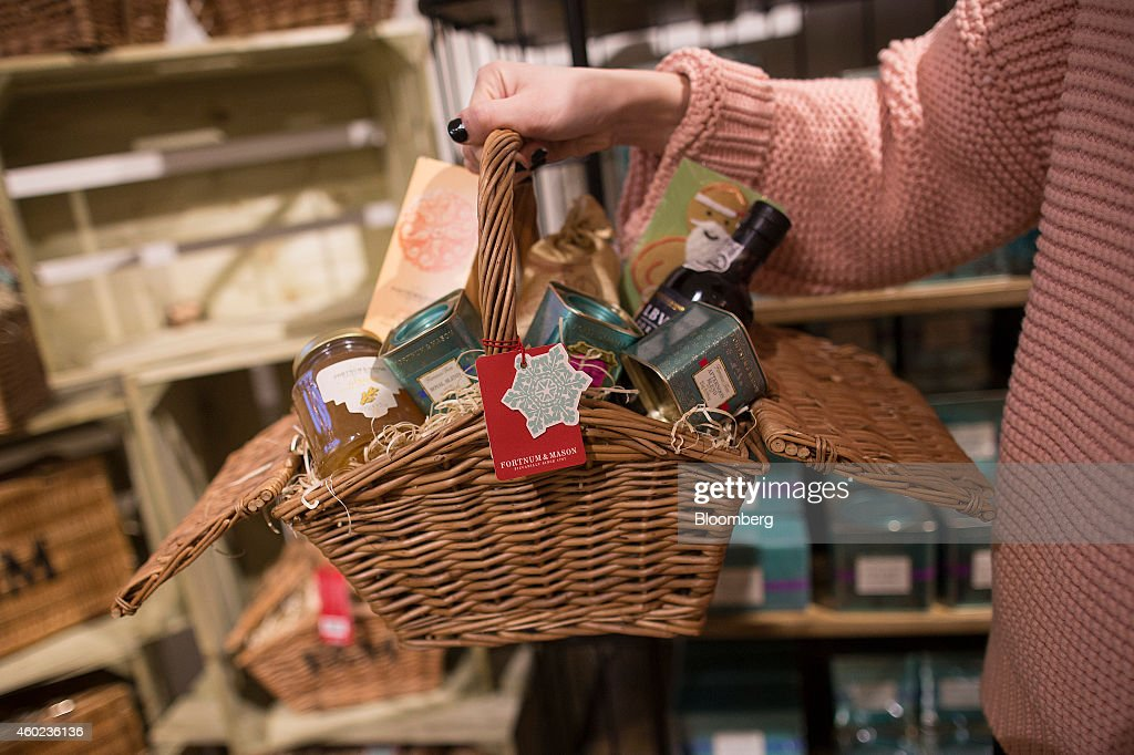 A shopper carries a festive hamper inside a pop-up store, operated by Fortnum & Mason Plc, during a seasonal Christmas event at Somerset House in London, U.K., on Tuesday, Dec. 9, 2014. The British will be the biggest spenders in Europe on Christmas gifts this year, according to a study commissioned by Dutch bank ING Groep NV. Photographer: Simon Dawson/Bloomberg via Getty Images
