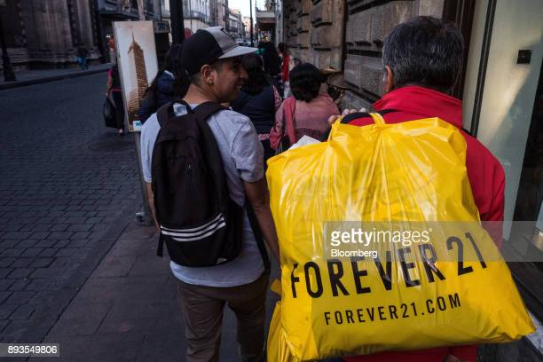 A shopper carries a Forever 21 Inc retail bag in Mexico City Mexico on Monday Nov 20 2017 The National Institute of Statistics and Geography is...