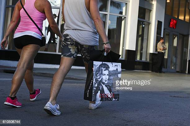 Shopper carries a Guess? Inc. Shopping bag at the Lincoln Road Mall in Miami Beach, Florida, U.S., on Wednesday, Sept. 21, 2016. The Conference Board...