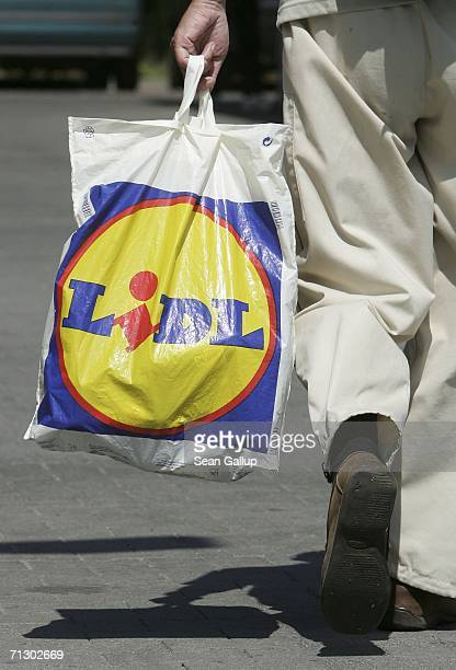 A shopper carries a Lidl shopping bag outside a Lidl supermarket June 27 2006 in Berlin Germany Germany's biggest service industry labour union Verdi...