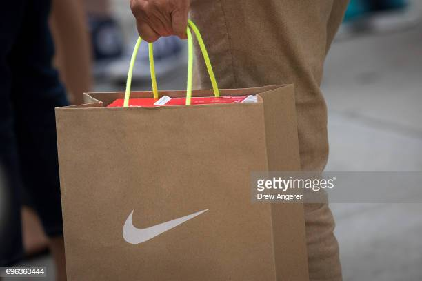 A shopper carries a Nike bag after leaving the Nike SoHo store June 15 2017 in New York City Nike announced plans on Thursday to cut about 2 percent...