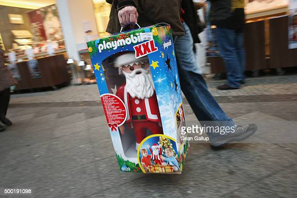 A shopper carries a Playmobil doll that looks like St Nicholas on a shopping Sunday on December 6 2015 in Berlin Germany Stores are usually closed on...