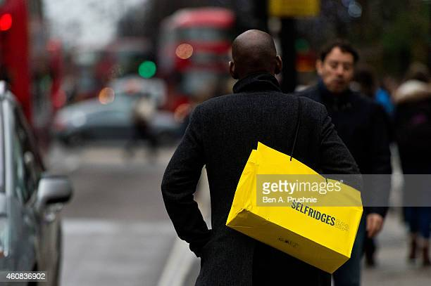 Shopper carries a Selfridges bag on Oxford Street during the annual boxing day sales on December 26 2014 in London England