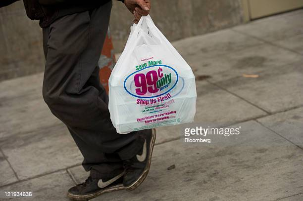 A shopper carries a shopping bag after leaving the 99 Cents Only Store in Oakland California US on Monday Aug 22 2011 99 Cents Only Store signage is...