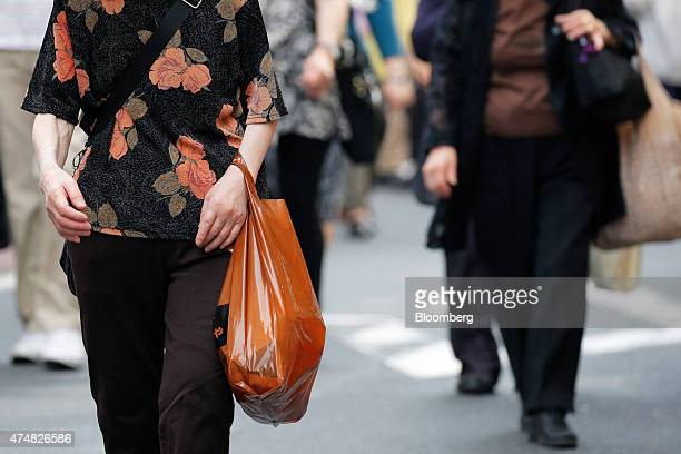 A shopper carries a shopping bag in the Sugamo district of Tokyo Japan on Sunday May 24 2015 Japan's Topix index fell for the first time in nine days...