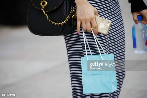 A shopper carries a Tiffany Co bag outside of the company's store on Rodeo Drive in Beverly Hills California US on Sunday Nov 26 2017 Tiffany Co is...