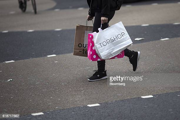 A shopper carries a Topshop Ltd shopping branded bag as they walk down Oxford Street in London UK on Thursday Oct 27 2016 Multiple reports show...