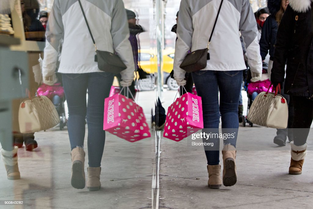 A shopper carries a Victoria's Secret Stores LLC Pink brand bag while walking through the Magnificent Mile commercial district in Chicago, Illinois, U.S., on Friday, Dec. 29, 2017. Bloomberg is scheduled to release consumer comfort figures on January 4. Photographer: Daniel Acker/Bloomberg via Getty Images