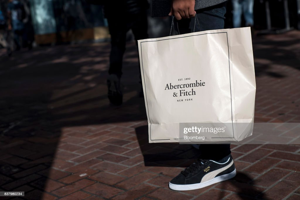 A shopper carries an Abercrombie & Fitch Co. bag while walking on Market Street in San Francisco, California, U.S., on Tuesday, Aug. 22, 2017. Abercrombie & Fitch Co. is scheduled to release earnings figures on August 24. Photographer: David Paul Morris/Bloomberg via Getty Images