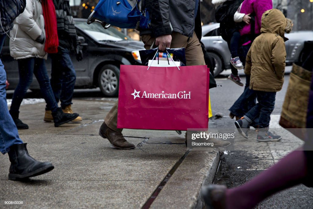 A shopper carries an American Girl Brands LLC bag while walking through the Magnificent Mile commercial district in Chicago, Illinois, U.S., on Friday, Dec. 29, 2017. Bloomberg is scheduled to release consumer comfort figures on January 4. Photographer: Daniel Acker/Bloomberg via Getty Images