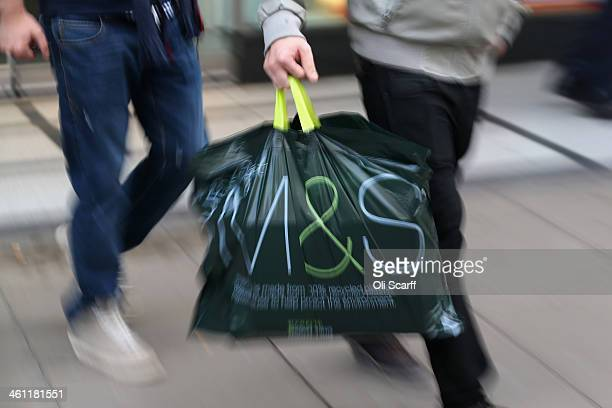 A shopper carries an MS bag out of a branch of Marks Spencer on January 7 2014 in London England The food and clothing retailer which has traded for...