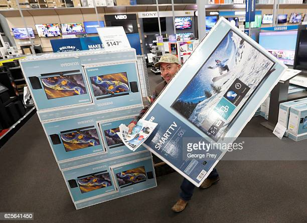 A shopper carries away a television at a Best Buy store that was on sale as part of 'Black Friday' deals on November 24 2016 in Orem Utah Retailers...