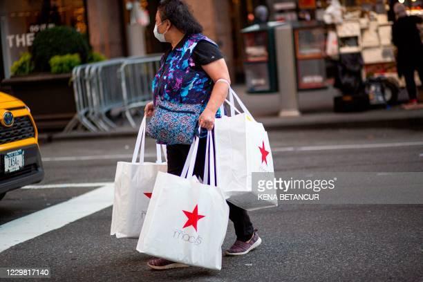 "Shopper carries bags as she leaves Macys department store in New York on Black Friday, November 27, 2020. - The coronavirus is clouding ""Black..."