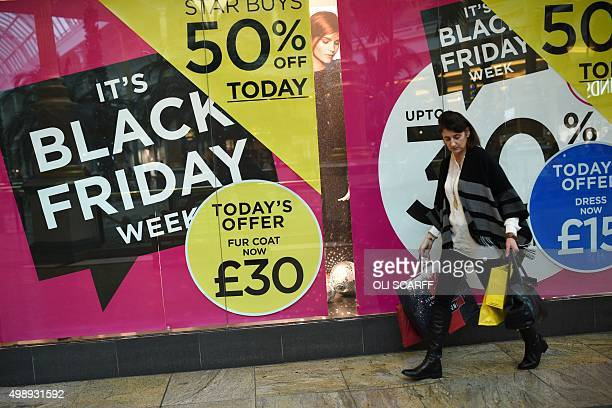 A shopper carries bags as she walks through the Trafford Centre shopping mall past retailers offering 'Black Friday' discounts in Manchester northern...
