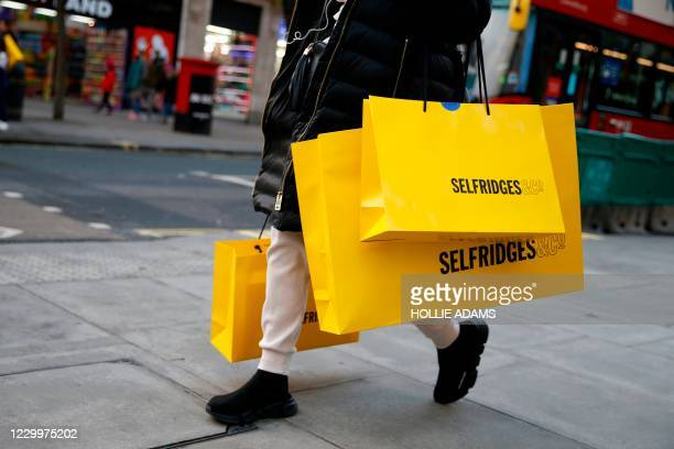 Shopper carries bags from department store Selfridges along Oxford Street on the Sunday afternoon in London on December 6, 2020. - Shoppers returned...
