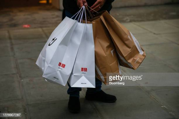 Shopper carries bags from Uniqlo and Zara in London, U.K., on Wednesday, Dec. 2, 2020. Most of England's retailers are emerging from lockdown, with...