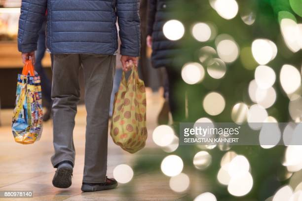 A shopper carries bags in a shopping center decorated for Christmas on November 28 2017 in Dresden eastern Germany Confidence among German consumers...