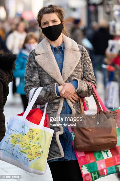 A shopper carries bags on Queen Street on Black Friday on November 27 2020 in Cardiff Wales Restrictions across Wales have been relaxed following a...