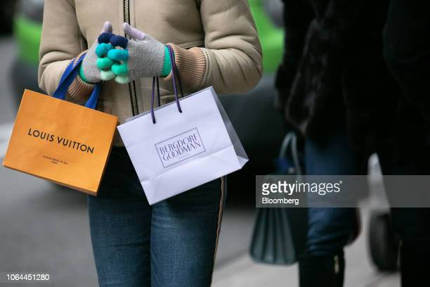 A shopper carries Bergdorf Goodman Inc and LVMH Moet Hennessy Louis Vuitton SE retail bags while walking along Madison Avenue in New York US on...