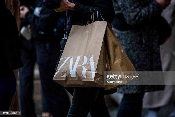 Shopper carries branded bags from a Zara clothing store, operated by Inditex SA, in Barcelona, Spain, on Monday, March 8, 2021. Inditex will report...