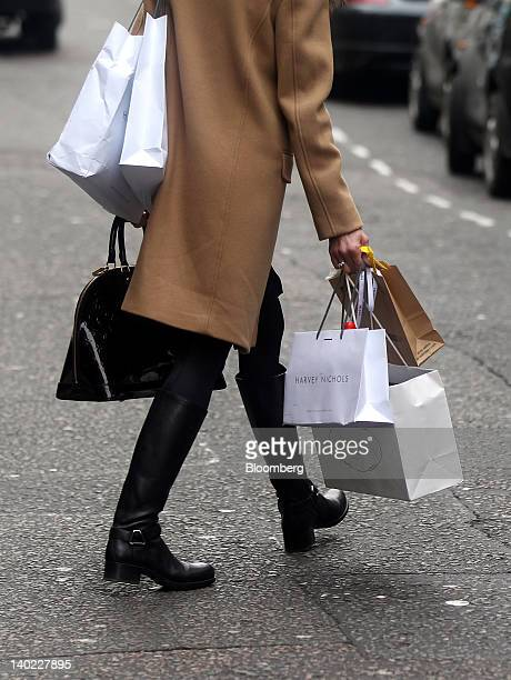 A shopper carries branded shopping bags from Harvey Nichols and the Prada SpA store as she walks along Old Bond Street in London UK on Wednesday Feb...