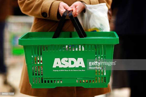 A shopper carries her purchases at an Asda store in Leyton east London UK on Wednesday Jan 14 2009 Asda WalMart Stores Inc's UKsupermarket chain said...