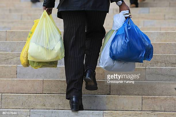 A shopper carries her purchases in plastic carrier bags through the city centre of Birmingham England on March 4 2008 The Prime Minister Gordon Brown...