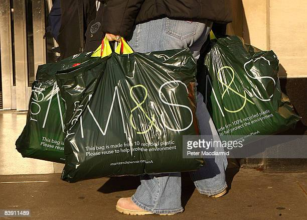A shopper carries Marks and Spencer department store bags in Oxford Street on the day of a 20 percent sale on December 4 2008 in London England The...