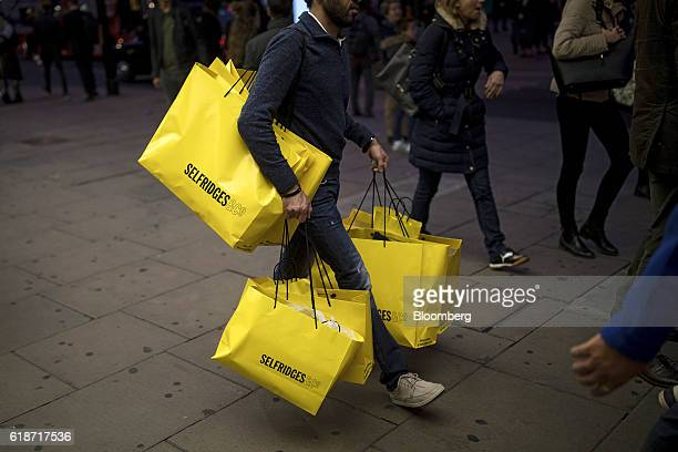 A shopper carries multiple branded shopping bags as he leaves the Selfridges Plc department store on Oxford Street in London UK on Thursday Oct 27...