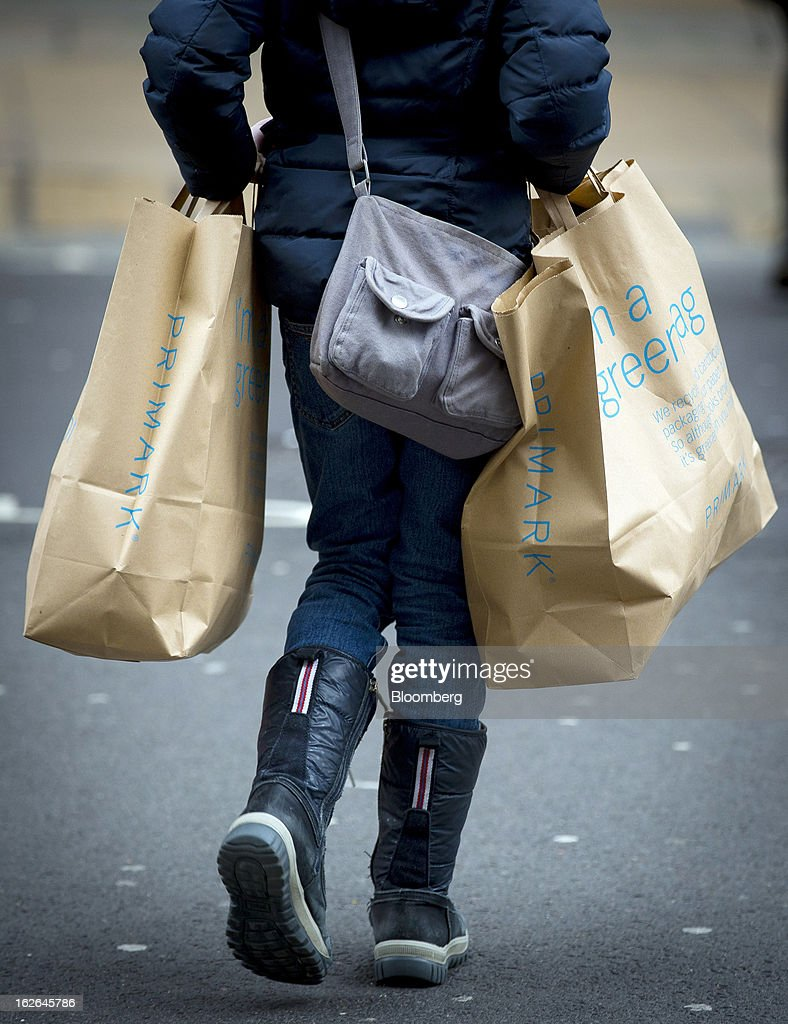 A shopper carries Primark shopping bags along Oxford Street, the store is operated by Associated British Foods Plc in central London, U.K., on Monday, Feb. 25, 2013. U.K. Chancellor of the Exchequer George Osborne won't bow to opposition calls to change economic plans after the decision by Moody's Investors Service to strip the U.K. of its Aaa status. Photographer: Jason Alden/Bloomberg via Getty Images