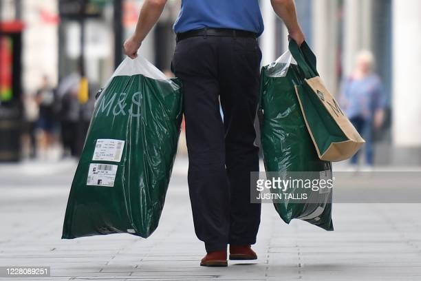 Shopper carries purchases after leaving a store of the clothing and food retailer Marks and Spencer in central London on August 18, 2020. - Marks and...