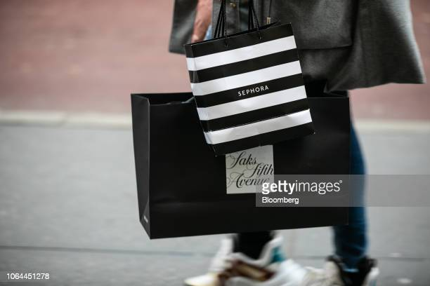 A shopper carries Saks Fifth Avenue Inc and Sephora USA Inc retail bags while walking along Madison Avenue in New York US on Wednesday Nov 21 2018...