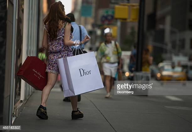 A shopper carries Salvatore Ferragamo SpA and Christian Dior SA bags while walking on Madison Avenue in New York US on Wednesday Sept 3 2014 The...