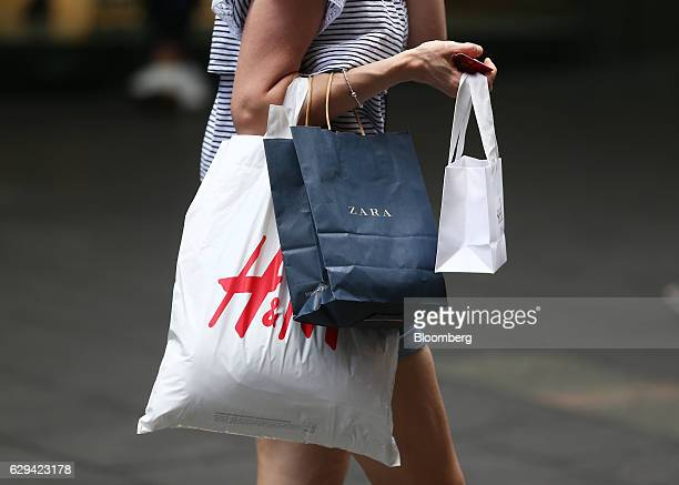 A shopper carries shopping bags by Zara operated by Inditex SA and Hennes Mauritz AB in Sydney Australia on Saturday Dec 10 2016 Australia is...