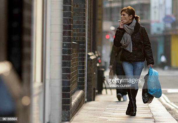 Shopper carries shopping bags in Covent Garden in central London, on January 26, 2010. Britain limped out of its longest ever recession in the fourth...
