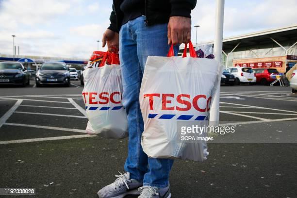 A shopper carries Tesco shopping bags as he leaves a Tesco Extra store in north London Thursday 9 Jan 2020 Tesco plc will publish its third quarter...