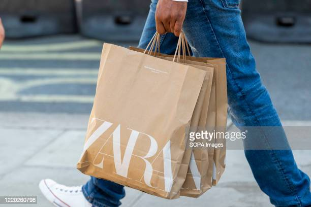 Shopper carries Zara shopping bags on Londons Oxford Street after the shops were allowed to reopen.