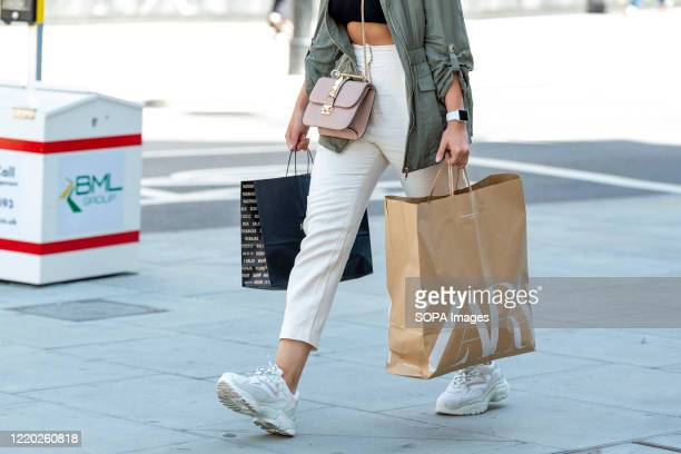 A shopper carries Zara shopping bags on Londons Oxford Street after the shops were allowed to reopen